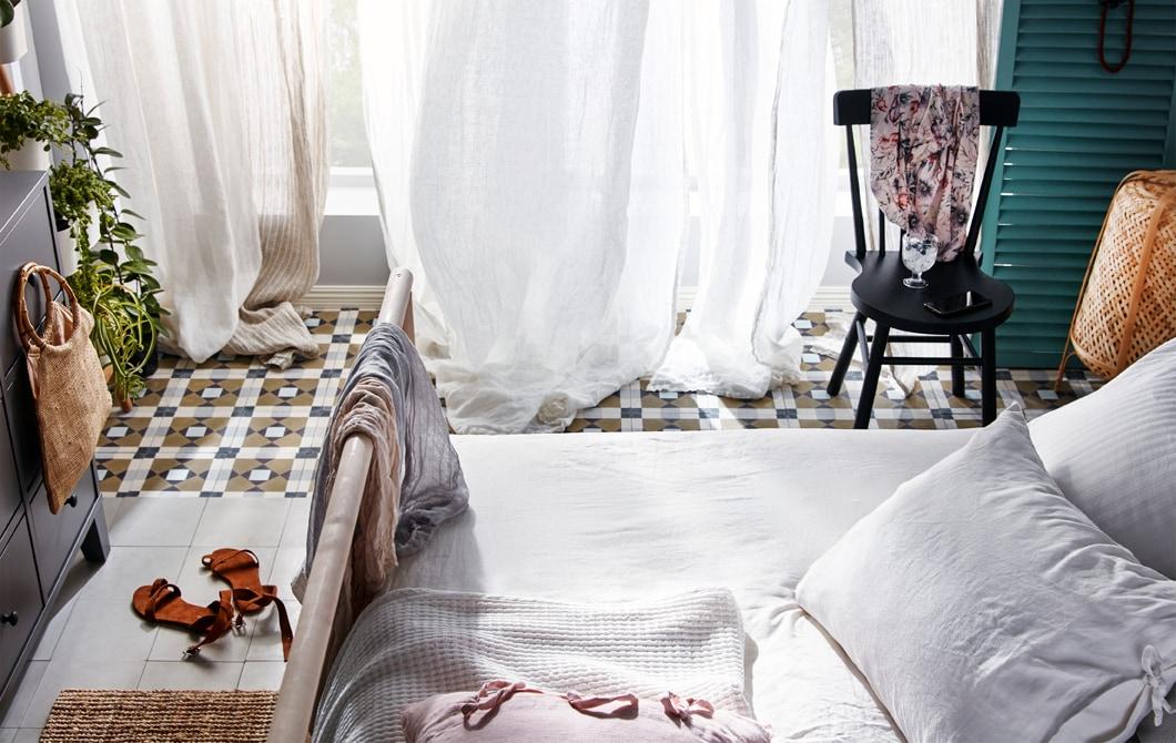 一间卧室内,装有落地窗,窗前挂着纱帘,微风从开着的窗户中吹进屋内,纱帘似乎正随风飘动。