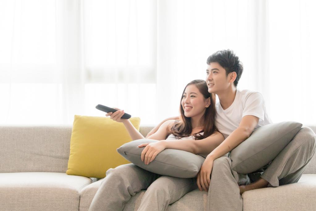 摄图网_500610000_banner_情侣在客厅沙发放松休闲看电视(非企业商用)