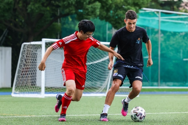 A couple of men playing football  Description automatically generated with medium confidence