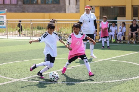 A couple of girls playing football  Description automatically generated with low confidence