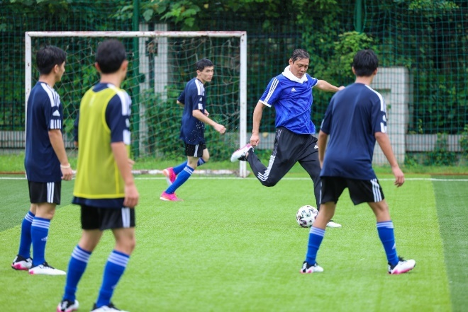 A group of men playing football  Description automatically generated with medium confidence