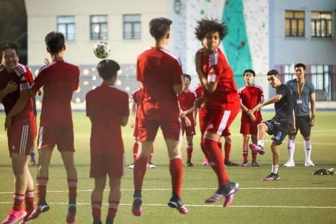 A group of people playing football  Description automatically generated with low confidence